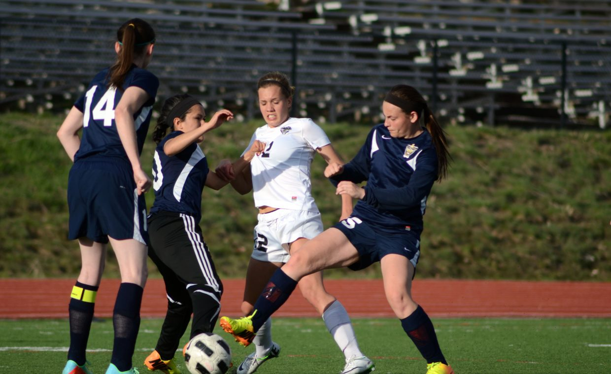Sophomore Natalie Bohlmann fights off a pair of Rifle players in the first half of the Sailors 7-0 win Thursday night.