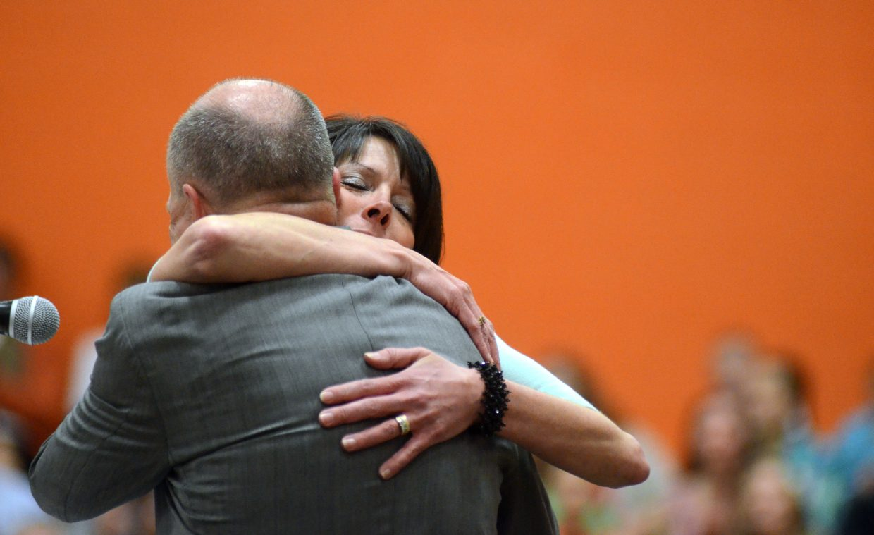 Hayden High School Principal Gina Zabel hugs retiring Superintendent Mike Luppes at Sunday's graduation commencement ceremony.
