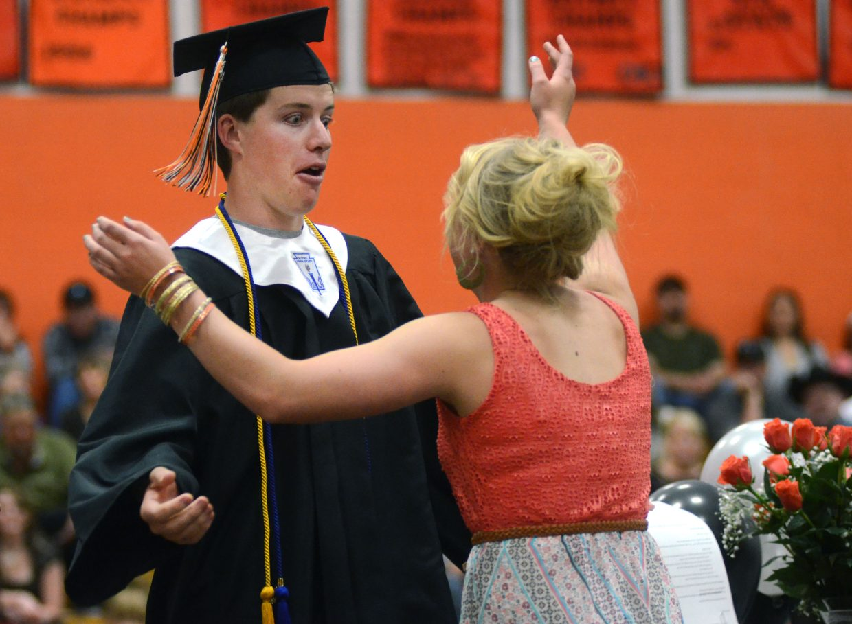 Hayden graduate Liam Delaney and junior Jordan Temple share a lighthearted moment onstage after Delaney accepted the student council scholarship at Sunday's graduation commencement ceremony.