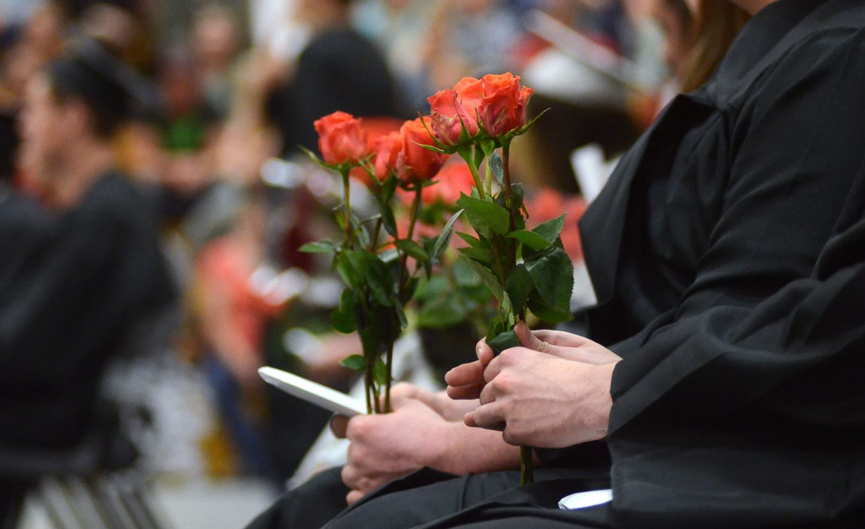 Graduating Hayden High School seniors hand out roses to family, friends and district staff moments before receiving their diplomas at Sunday's commencement ceremony.