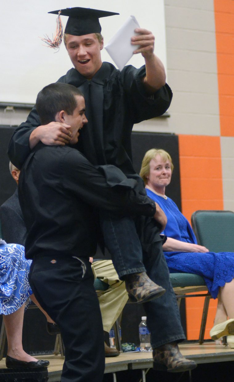 Hayden graduate Journey Vreeman leaps onto a friend after receiving his diploma at Sunday's commencement ceremony.