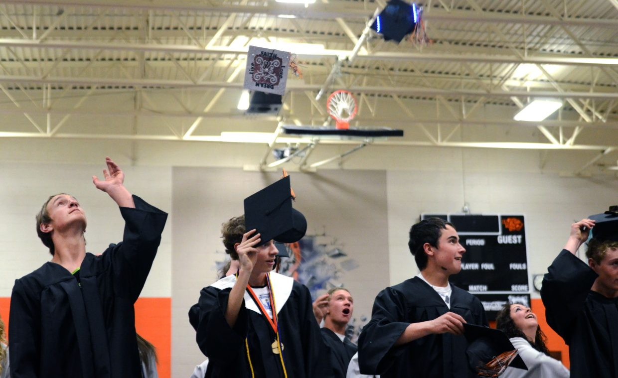 Hayden graduates toss their caps into the air after officially graduating from high school Sunday.