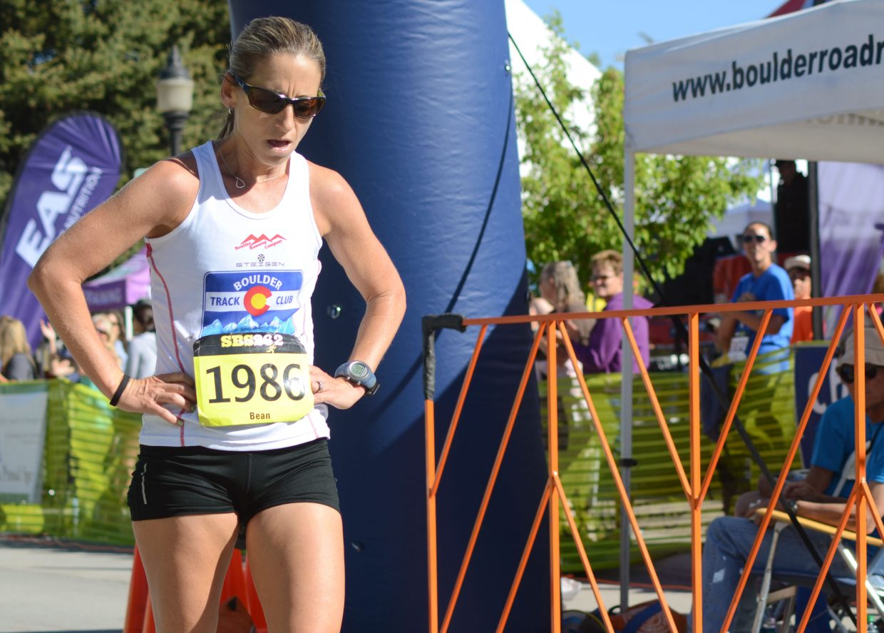 Boulder's Bean Wrenn catches her breath after crossing the half-marathon finish line in first place Sunday.