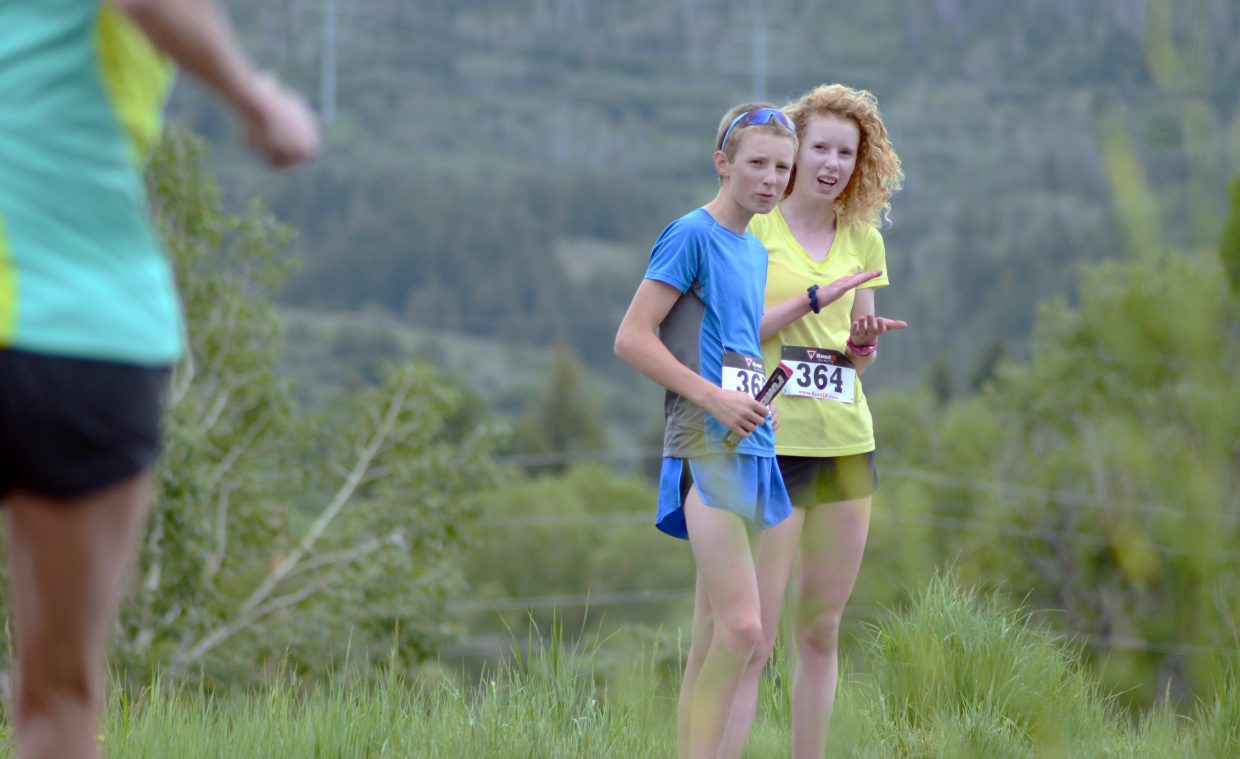 Tyler and Tabor Scholl cheer on finishers in the Howelsen Hill 8-Miler during Saturday morning's Steamboat Springs Running Series race. The siblings finished the 4-mile race well ahead of the pack and hiked back up the trail to root for racers.