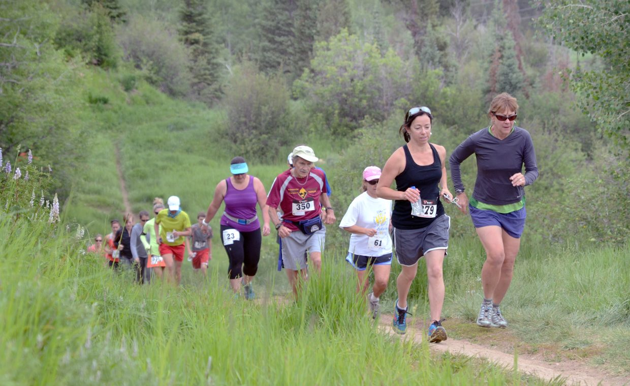 Middle-of-the-pack runners make a steep early climb along the Bluffs Loop on Emerald Mountain during the Howelsen Hill 4- and 8-mile races Saturday morning.