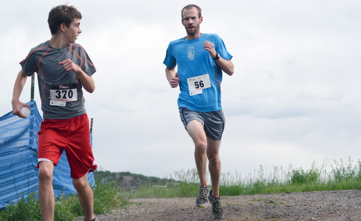 Paul Moth, right, startles a 4-mile runner during Moth's Howelsen Hill 8-Miler victory Saturday morning.