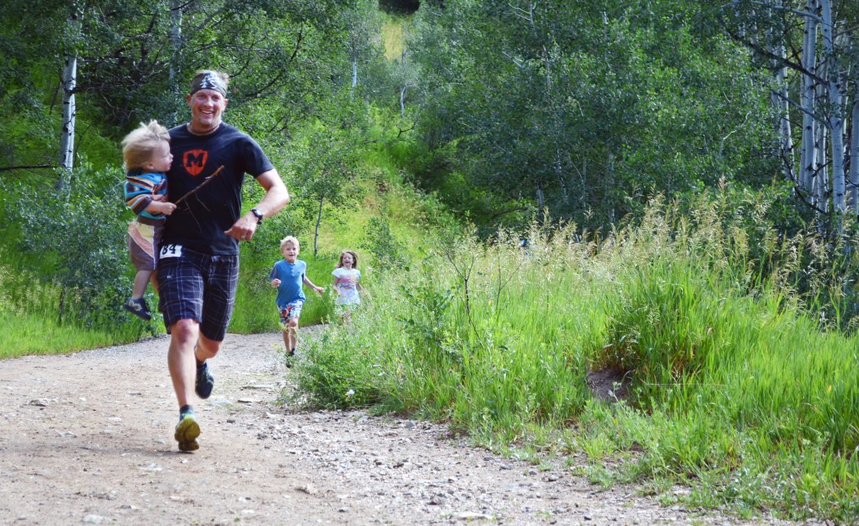 Andy Picking carries and is chased by his children while approaching the finish in the 9-miler Saturday at the Spring Creek Memorial race.