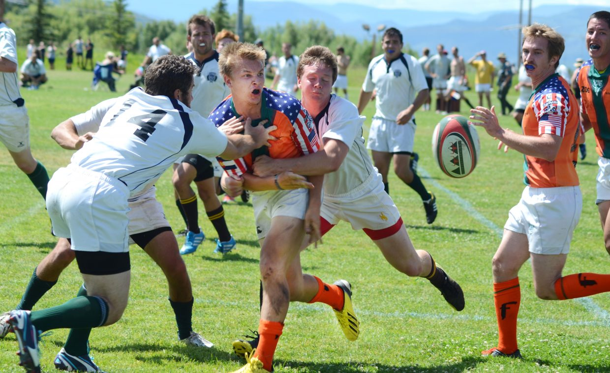 Steamboat's Nigel Hammond laterals to a teammate just before a score in the first half of the team's 22-7 win against Jackson Hole, Wyoming, in Saturday's Cow Pie Classic Rugby Tournament.
