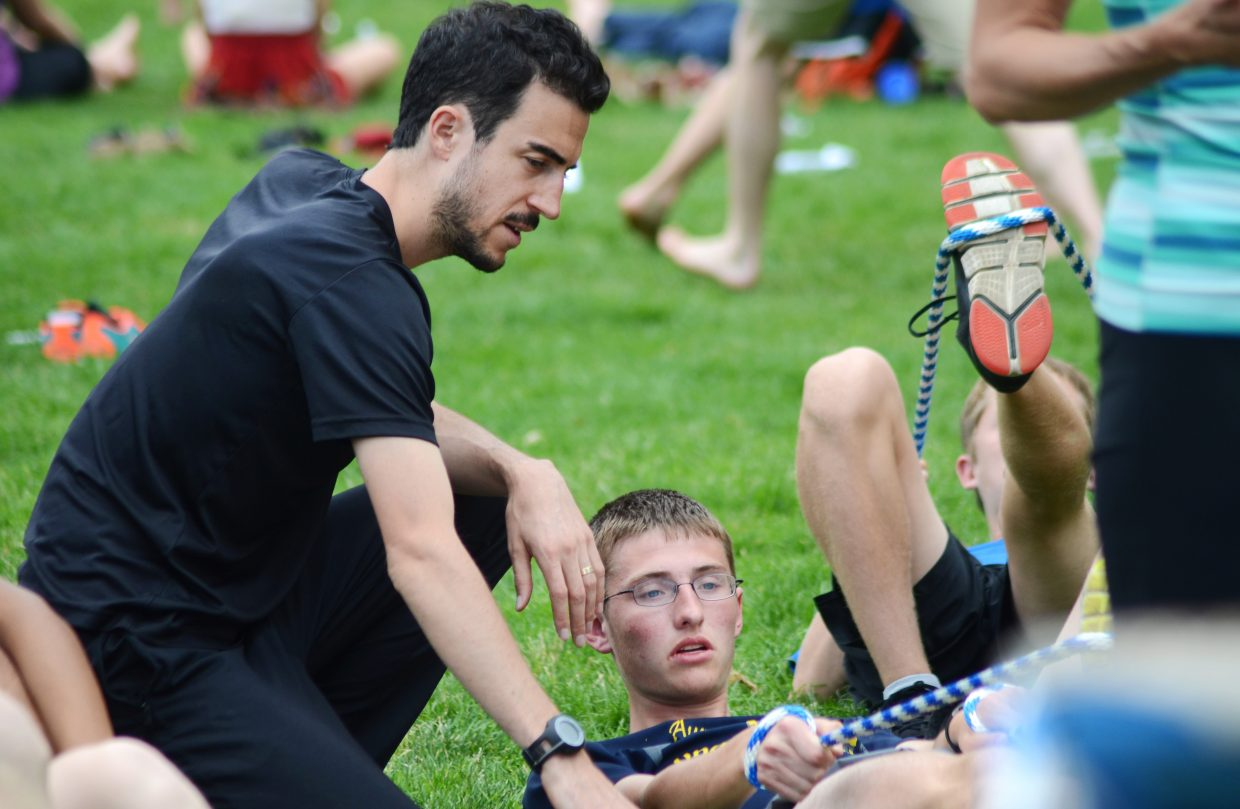 Run SMART Project founder Brian Rosetti coaches Roosevelt High School's (S.D.) Lukas Nelson on some active isolated stretching Friday afternoon at Little Toots Park in downtown Steamboat Springs. The Run SMART high school running camp was back in Steamboat for a second summer, teaching students from across the country different elements of the sport.