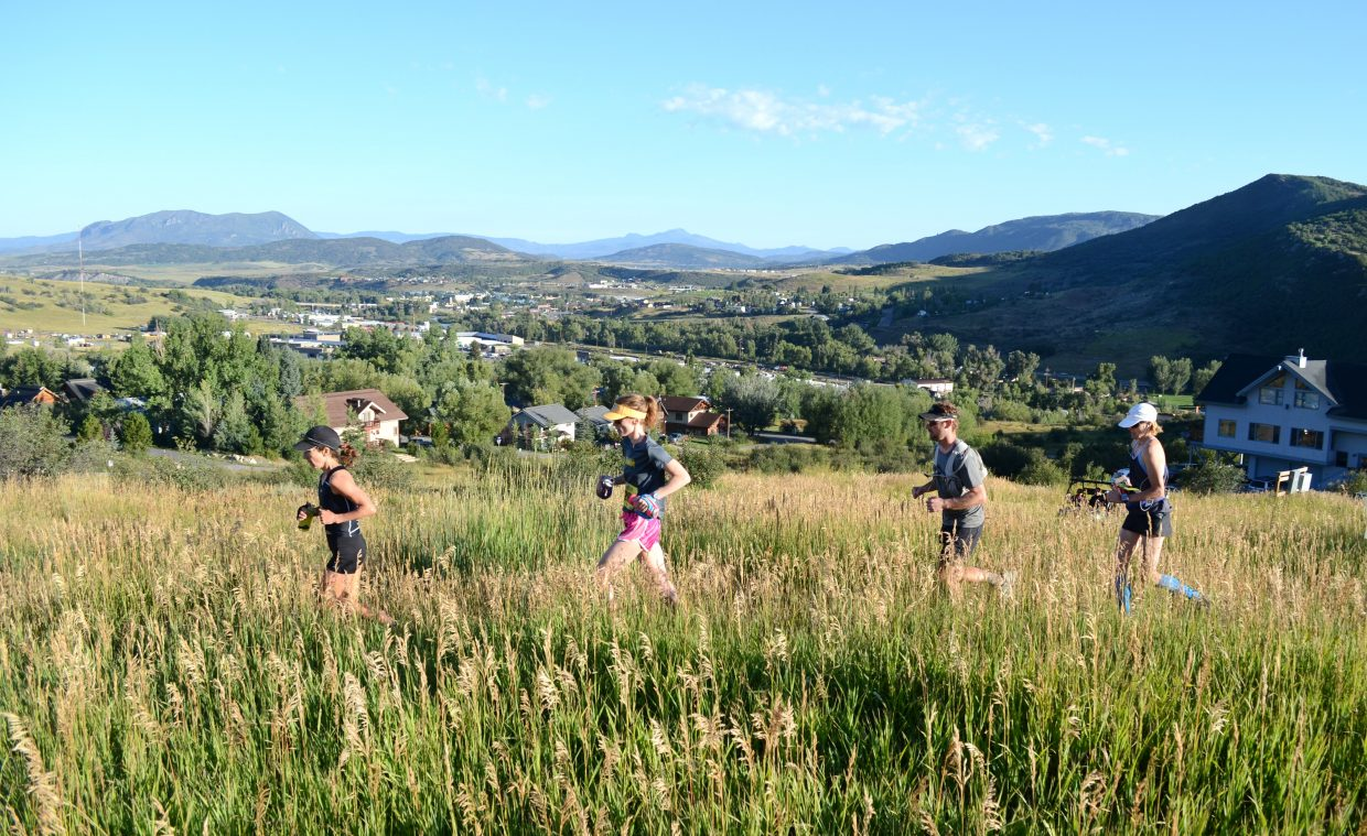 Runners in the Steamboat Stinger full marathon head through a meadow Sunday on their way to the top of Emerald Mountain.