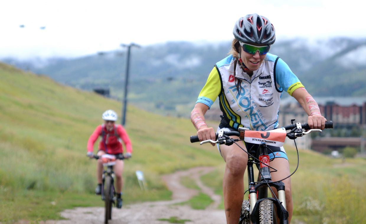 Marnie Pearsall climbs up a muddy Zig-Zag trail at Steamboat Ski Area in Sunday's Xterra All-Women's Off-Road Triathlon. Muddy conditions with happy racers marked the inaugural event.