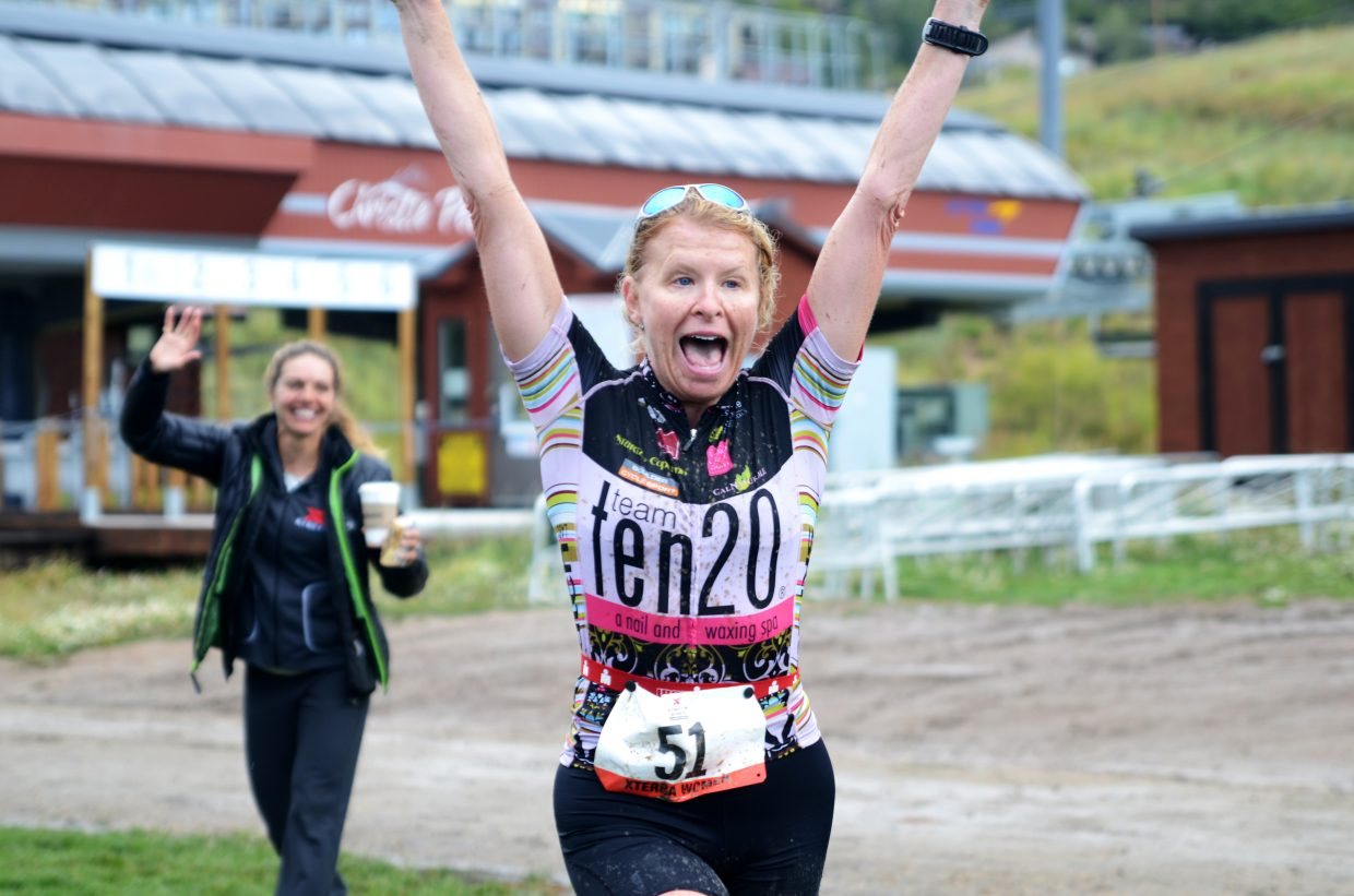 Westminister's Elizabeth Engler, cheered on by co-race director Heather Gollnick, is elated to see the finish line during the Xterra All-Women's Off-Road Triathlon sprint distance.