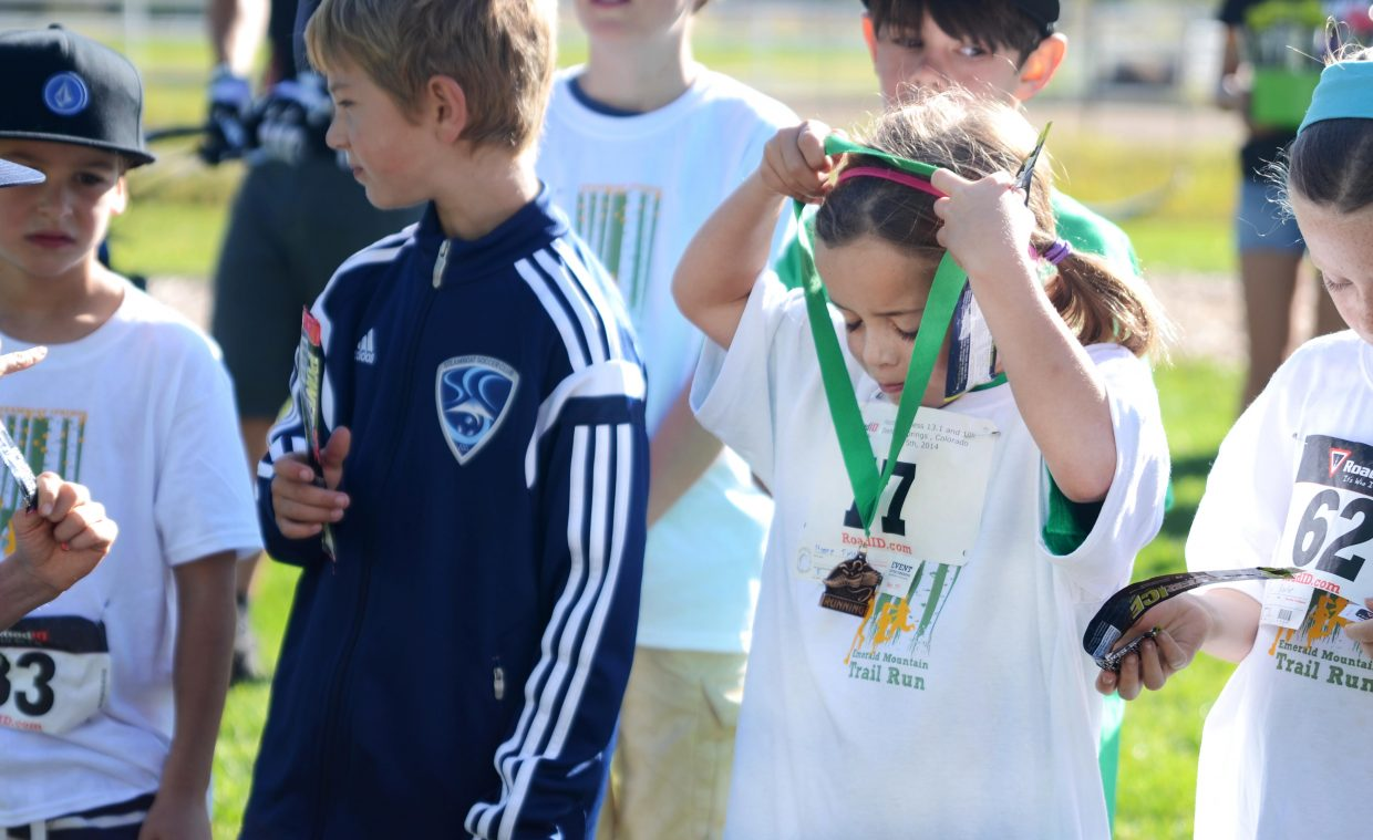 Emerald Mountain School student Tinsley Moore, 8, throws on her medal after the Emerald Mountain Trail Run kids 1-miler Saturday morning.