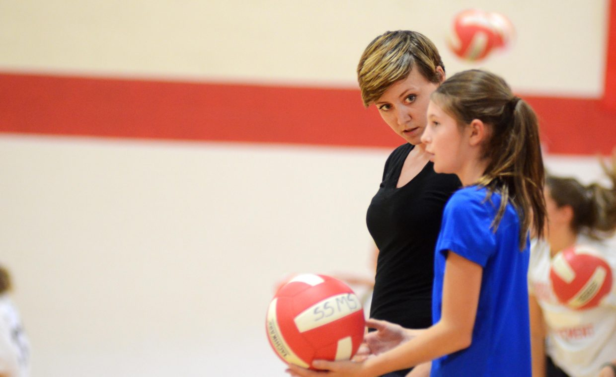 Steamboat Springs Middle School volleyball coach Tara King helps Samantha Kennedy with a serving drill during Friday's practice. King took over the program this year and brought with her a wealth of coaching and playing experience from overseas.