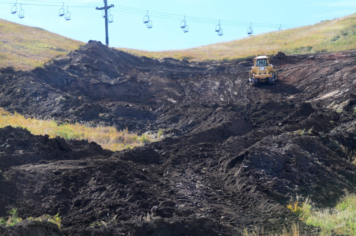 A tractor moves to spread out dirt and patch Howelsen Hill back together last week. As a result of a mud slide in the spring, the city with a little help from the Steamboat Springs Winter Sports Club have been moving quickly this month to get the ski hill back in shape for snowmaking next weekend and skiing in a month.