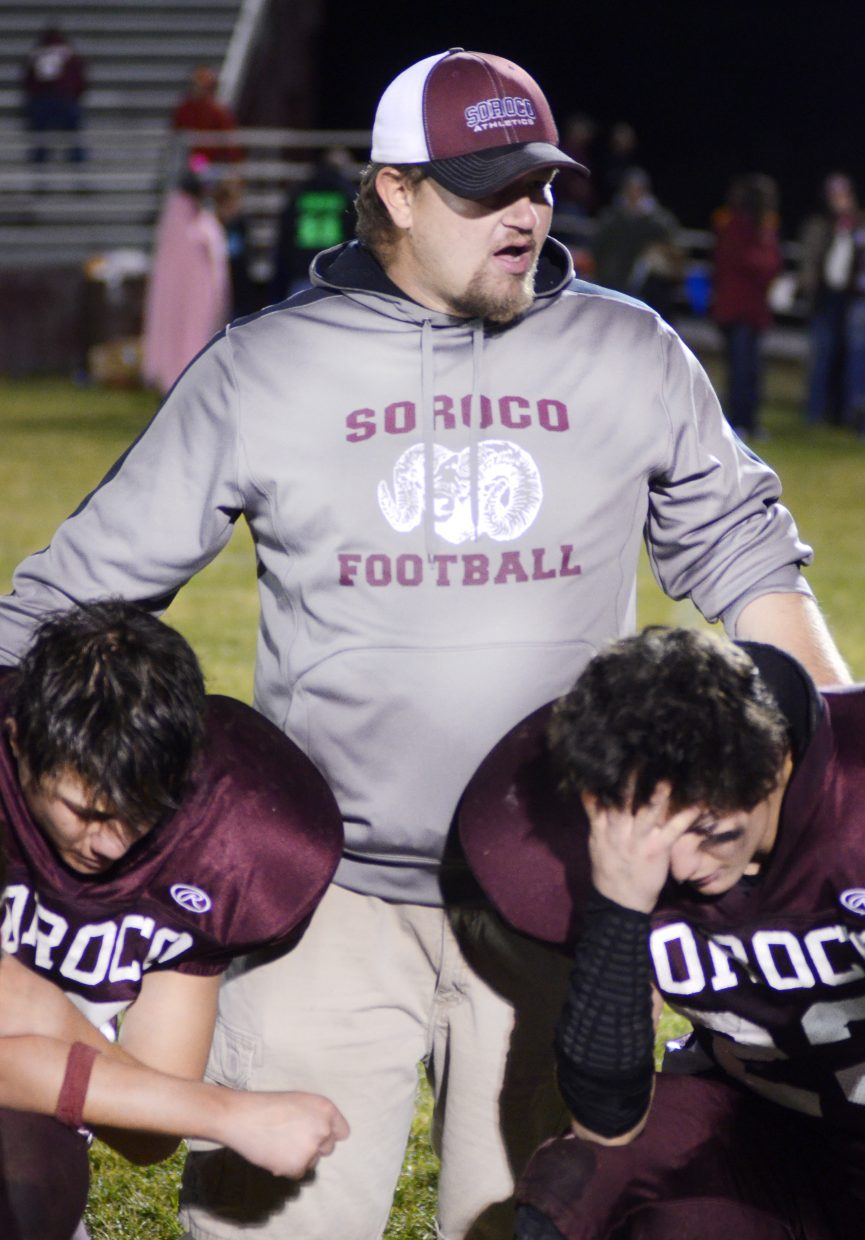 Soroco High School football coach Josef Keller — flanked by seniors Micah Gibbons and Carl Rossi — addresses his team after their 43-6 win against rival Hayden on Friday night in Oak Creek.