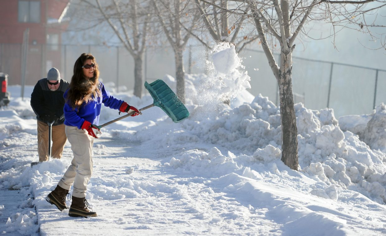 Steamboat Springs' Betsy Frick moves quickly to shovel a mix of snow and ice from the starting line of the 2014 Steamboat Springs Turkey Trot on Thanksgiving morning.