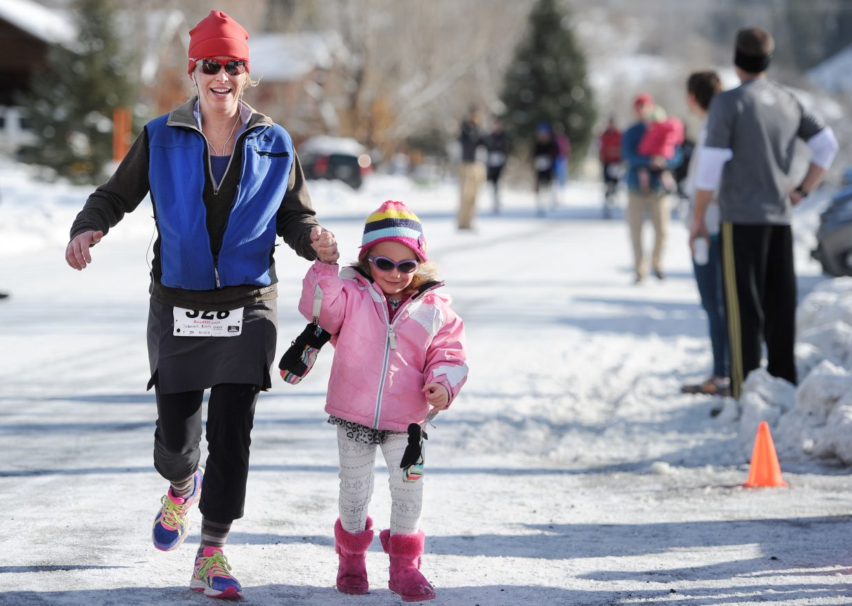 Erin Dickerson helps her daughter Josie Dickerson across the finish line at the 2014 Steamboat Springs Turkey Trot.
