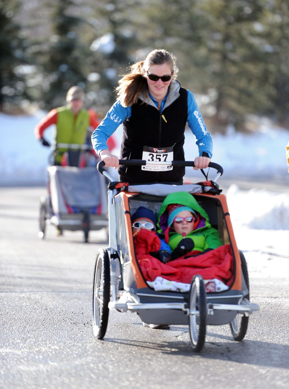 Valerie White pushes along her children Ayla, 4, and Lawson, 2, during the 2014 Steamboat Springs Turkey Trot.