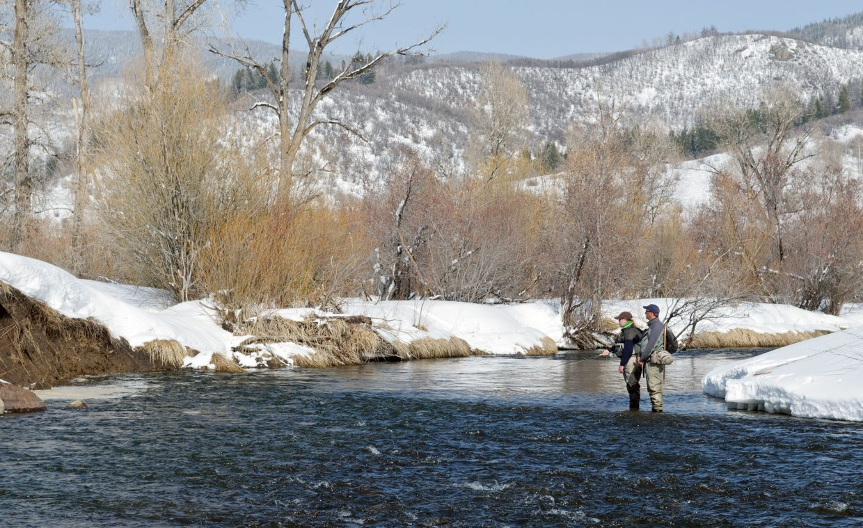 Steve Henderson and a client scour the snow-lined Yampa River private waters above Lake Catamount.