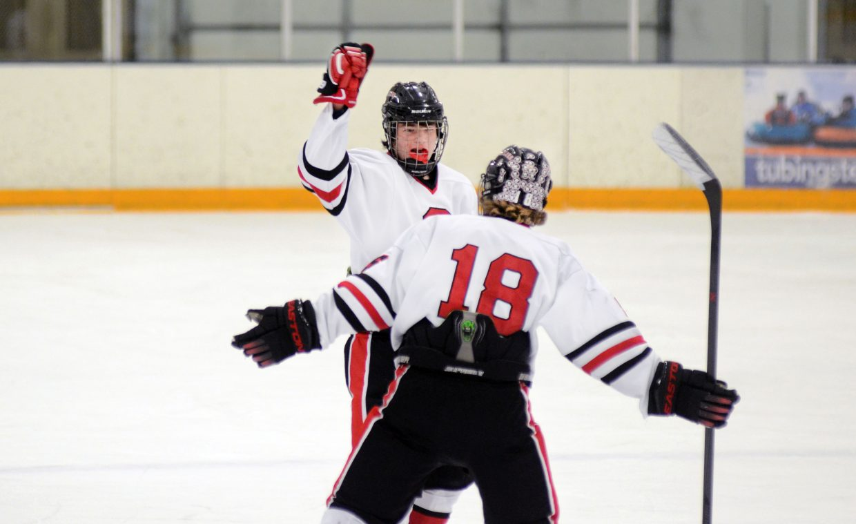 Steamboat Springs' Andrew Mitchell celebrates his first-period goal against Battle Mountain with teammate Jordan Gorr, No. 18, on Friday. Mitchell and the Sailors couldn't steal a win from the Huskies, but they did notch their first victory on Saturday against Kent Denver.