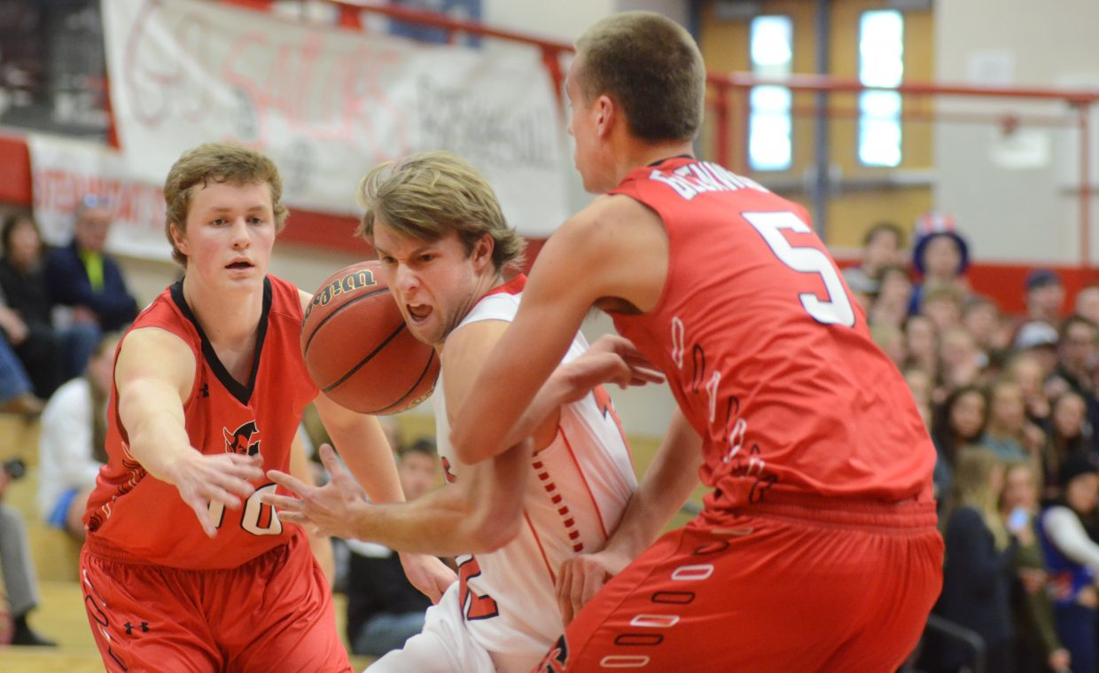 Steamboat Springs senior Nathan DePuy drives the lane between Glenwood Springs' Brian Burbidge and Zack Peterson in the first half of the Sailors' 45-38 loss on Saturday. The loss drops Steamboat into second place in the 4A Western Slope League. The two teams will meet again on Feb. 14 at Glenwood.