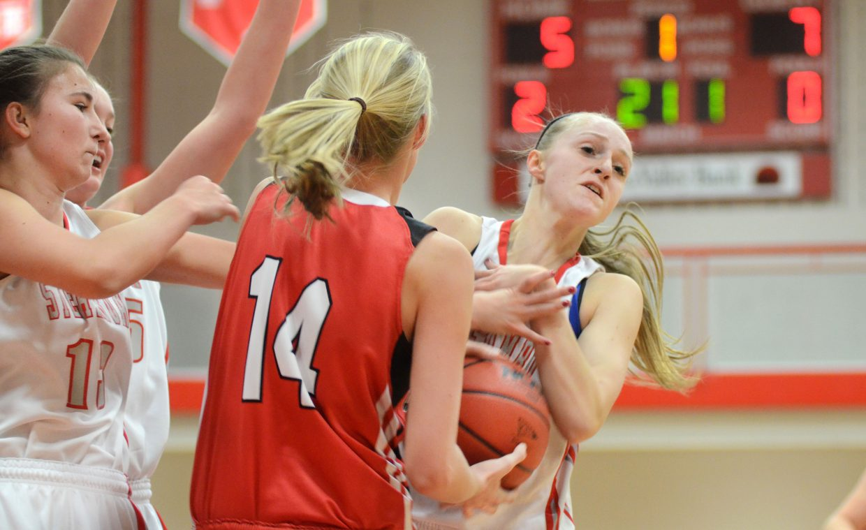 Glenwood Springs' Madi Spence gets in a wrestling match for the ball with Steamboat Springs' Kady Look.