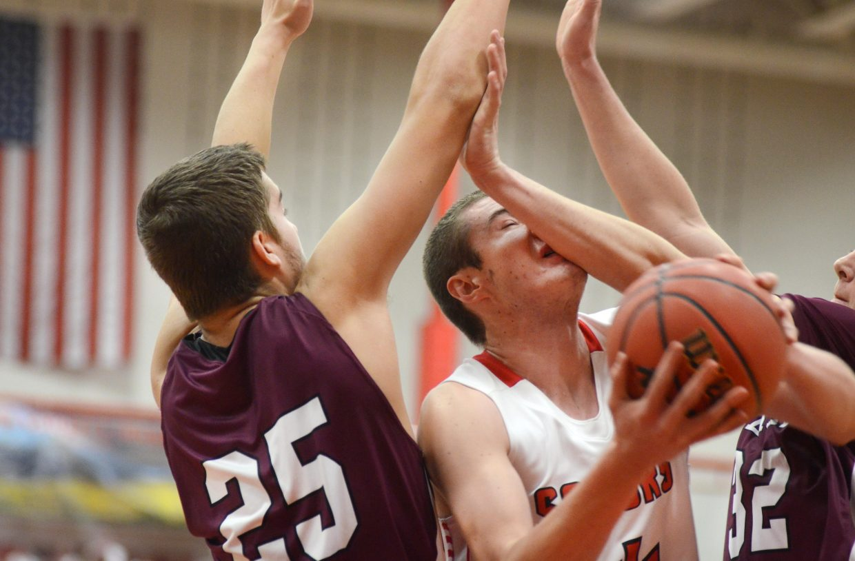 Steamboat Springs center Garrett Bye gets fouled hard by Palisade's Ian Schierland and Travis Thiessen.