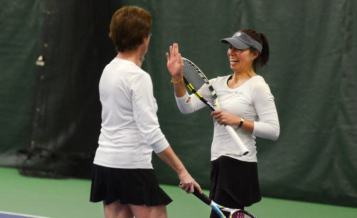 Stacy Swiggart and Lilia Snape come together for a high five in between points at Saturday night's Battle of the Sexes at the Tennis Center at Steamboat Springs. Snape, the Tennis Center's newest professional instructor, got to showcase some of her skills for the community.