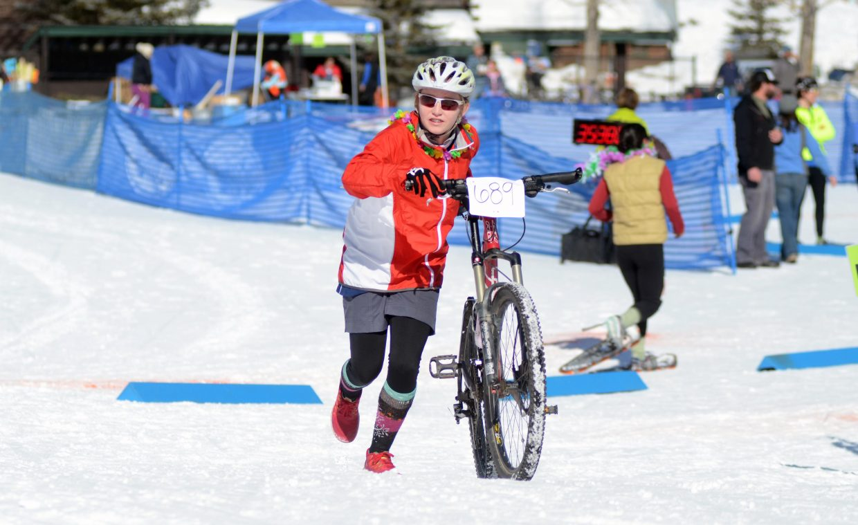 Annika Belshaw runs out her bike for her team, the Fab 5 Seventh Graders, during Sunday's Steamboat Pentathlon.
