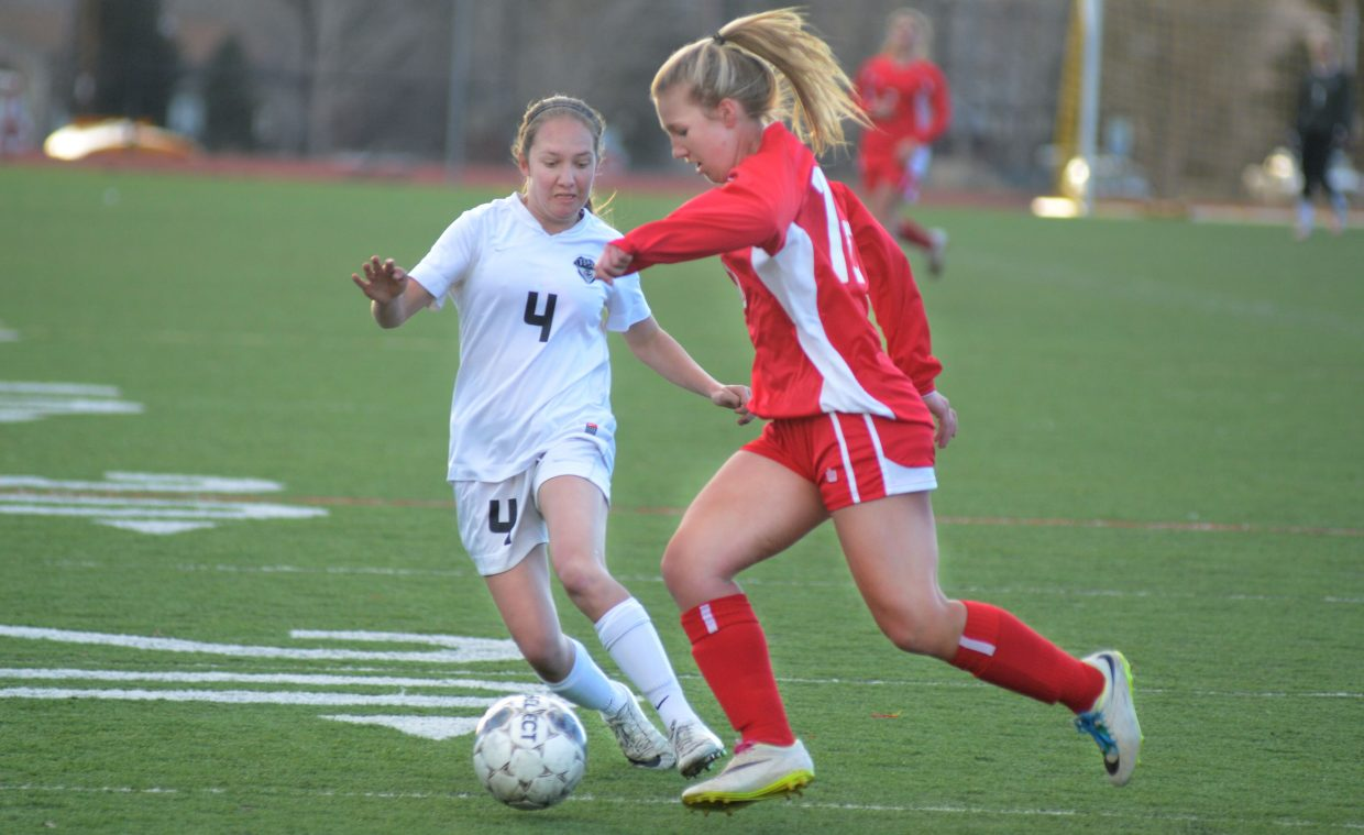 Steamboat Springs' Meghan Garrecht-Connelly, No. 4, tightly guards Glenwood Springs' Quincy Dollahan.