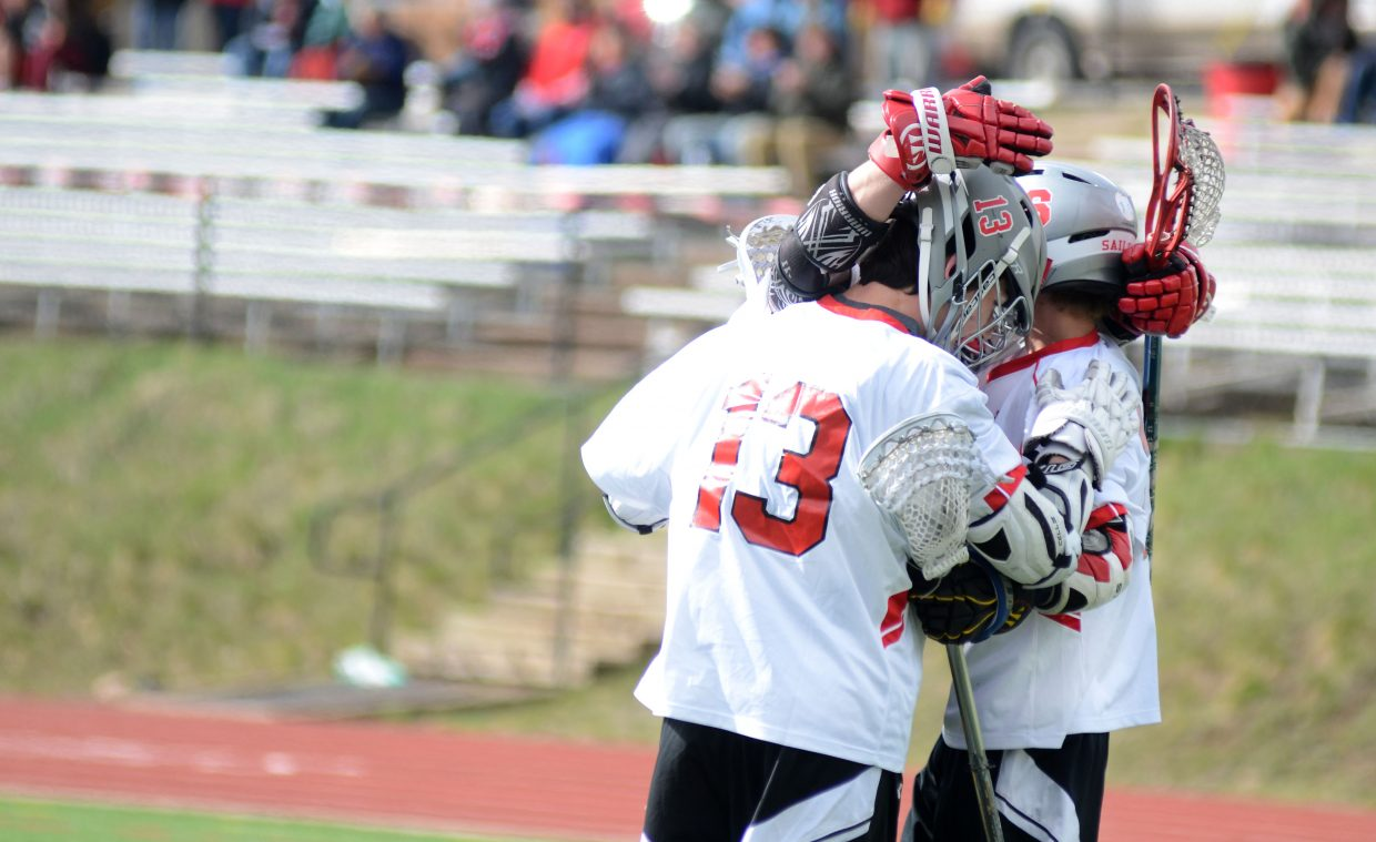 Three Steamboat Springs High School boys lacrosse players celebrate a first-quarter goal Thursday night versus Summit.