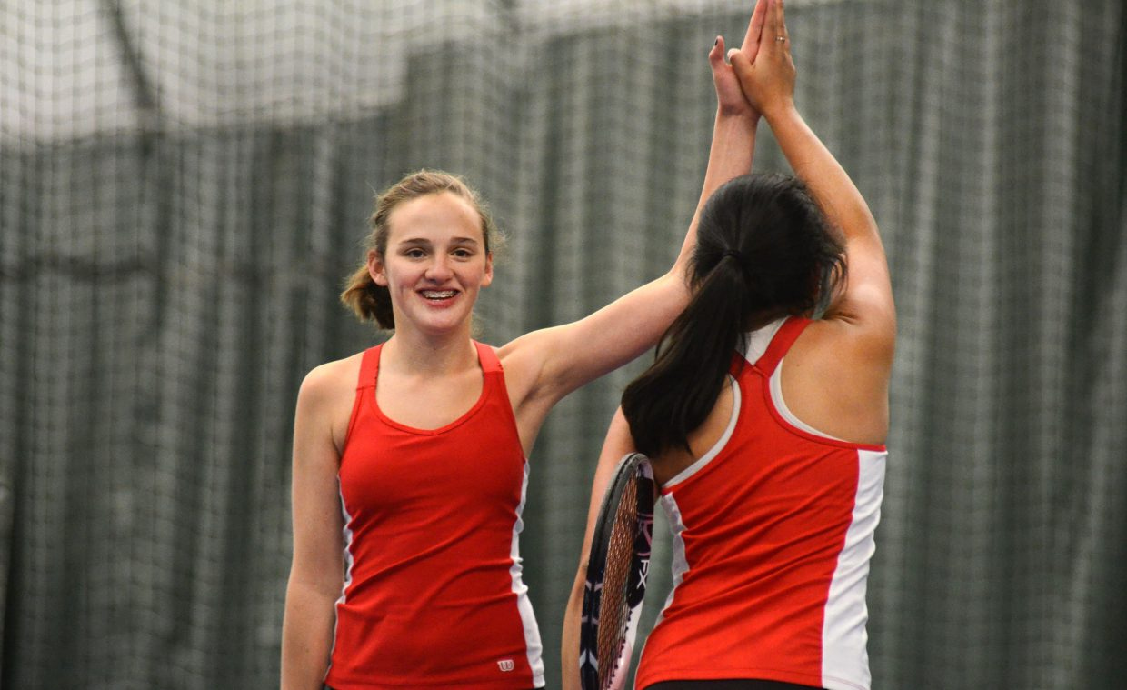 Steamboat Springs' Shae Burger high-fives No. 3 doubles teammate Norma Techarukpong during their match against Lakewood on Saturday.