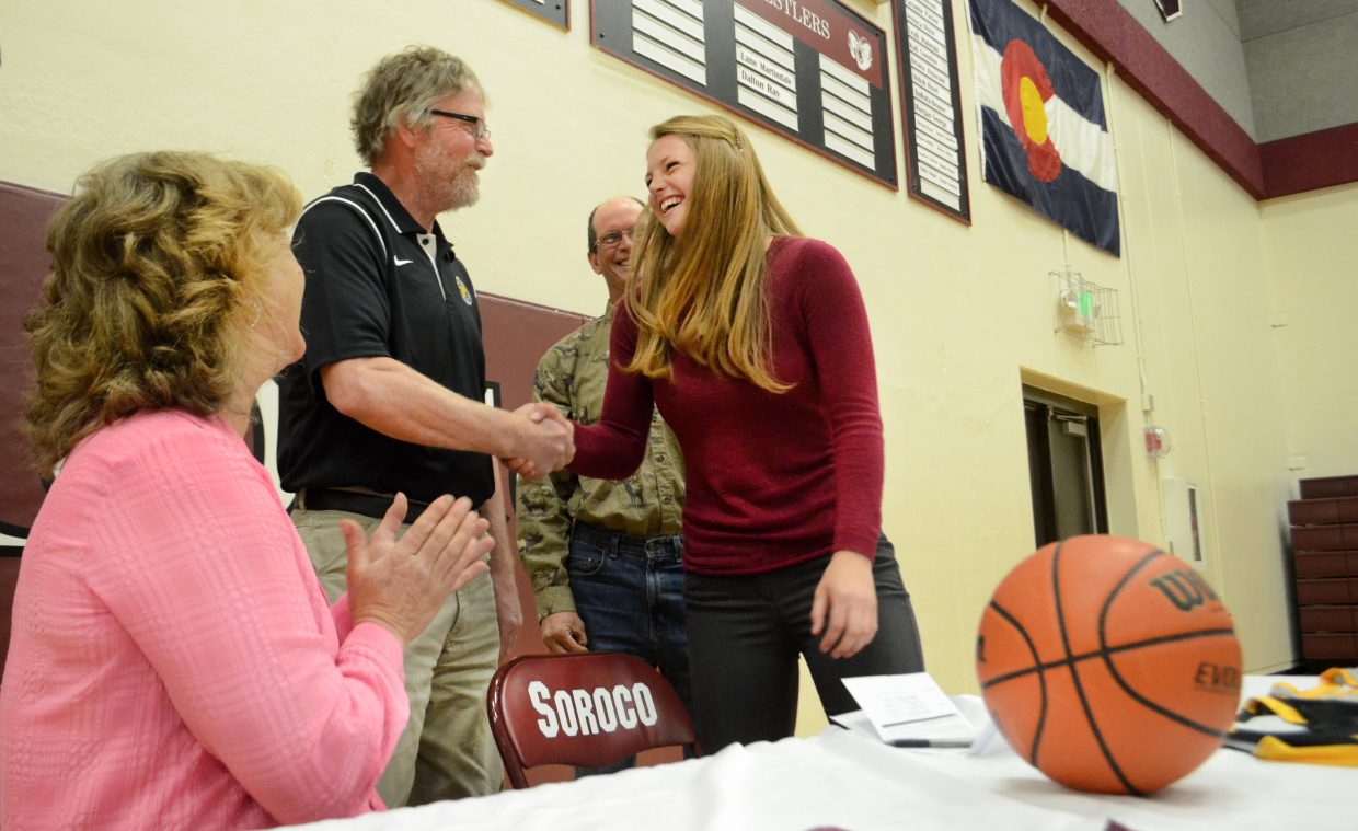 Soroco High School senior Jessica Rossi shakes Eastern Wyoming College women's basketball coach Tom Andersen's hand after she officially signed to play for the Lancers next season. The high school held a signing ceremony Thursday for Rossi, who averaged 16 points and nine rebounds in her final season for the Rams.
