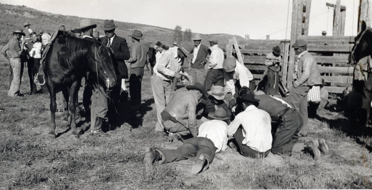 Cowboys participating in the rodeo at the Routt County Fair in the 1940s took time away from the action to play a dice game just outside of the livestock pens.