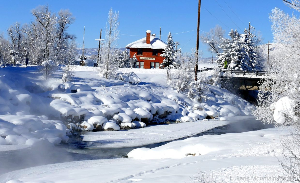 """Pictured is the train depot in Steamboat, with the frozen Yampa River in front. To the left and in the middle is the actual Steamboat Spring, for which the town is named. The railroad tracks are also right there. When the railroad came in to build the tracks, they had to move the rocks around, and the noise of a """"steamboat"""" was no longer there. That was back in the early 1900s.   http://www.ghostdepot.com/rg/mainline/moffat%20route/steamboat.htm """"The name of Steamboat Springs was given to the area by a group of fur trappers heading down the Yampa River. They heard a chugging sound, and thought it was a steamboat coming up the river, but it turned out to be the sound of the hot springs bubbling up out of the ground.""""   """"The arrival of the Denver Northwestern and Pacific railroad on December 13, 1908 was extremely important to the growth and development of Steamboat Springs. A marching band met the first train as it chugged into town, and hundreds of residents were waiting for the train at the depot, cheering it on. One negative of the railroad was that when the railroad grade was constructed across the springs the town was named after, the steamboat sounds were silenced forever.""""  Submitted by Shannon Lukens."""