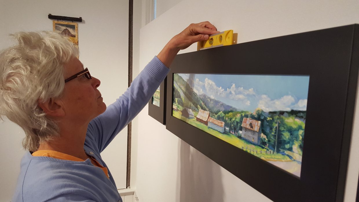 """Artist MB Warner hangs her paintings of local historic ranches at the Depot Art Center for the newest show, """"Barn Raising,"""" sponsored by the Steamboat Springs Arts Council"""