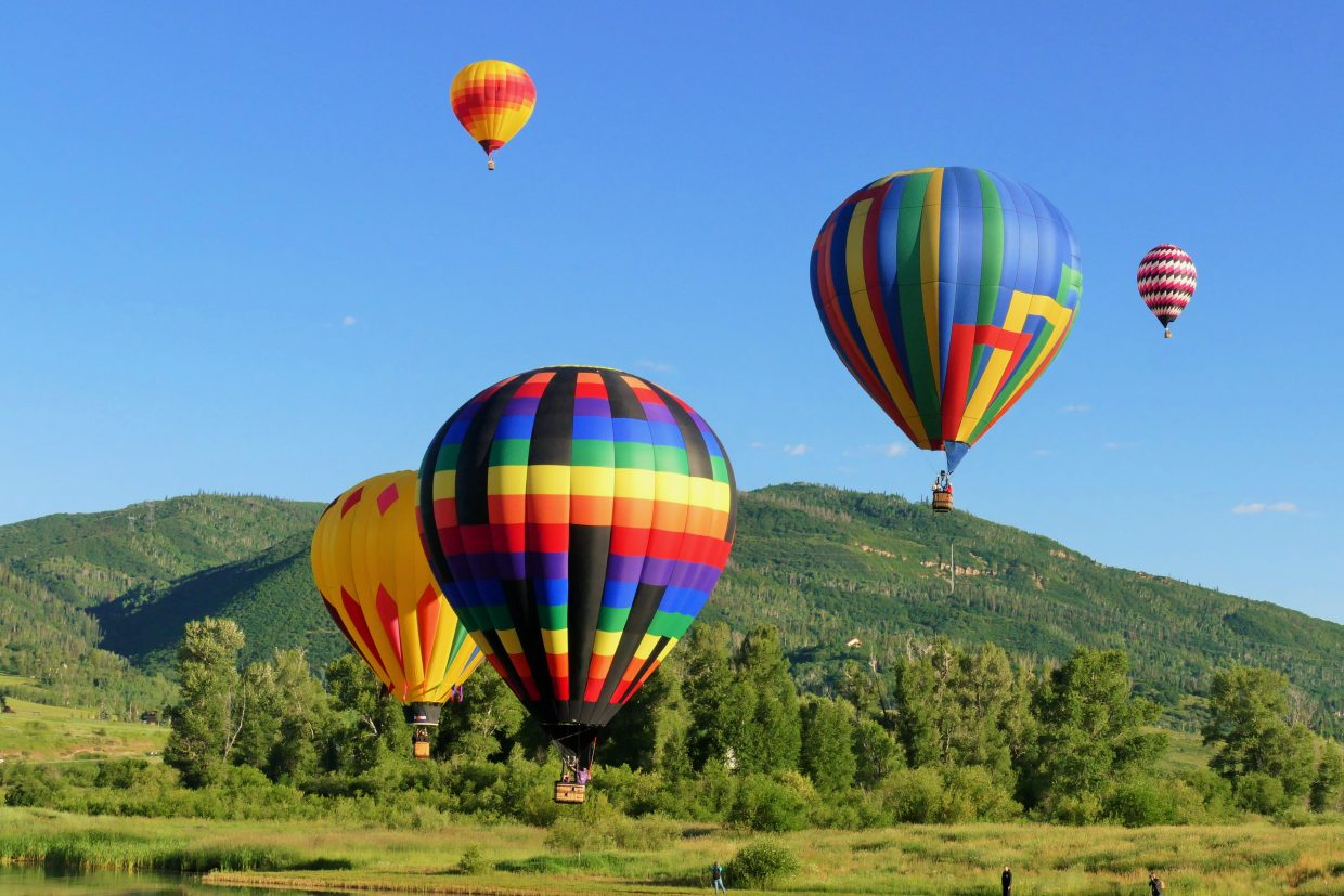 Here are a few pictures from today's 35th Annual Hot Air Balloon Rodeo in Steamboat Springs, which is also happening Sunday morning, starting at 6 a.m. These pictures were taken from Bald Eagle Lake in Steamboat. I am the announcer for the event.   The first picture (014) is of the two hand-painted balloons in the Balloon Rodeo. There are only 12 hand-painted balloons in the world and these are two of them. The circus balloon is called Big Top and the cowboy balloon is called Western Spirit.   The second picture is a nice balloon shot except there was a man there with a unicorn head watching. It was interesting. I had to take his picture.   The third shot (003) is the Colorado High Balloon which is the Colorado state flag, and then the American Flag balloon, heading out over Bald Eagle Lake.   The next shot is five balloons over Bald Eagle Lake.   The last shot (002) shows the sun coming up behind the mountain. Submitted by Shannon Lukens.