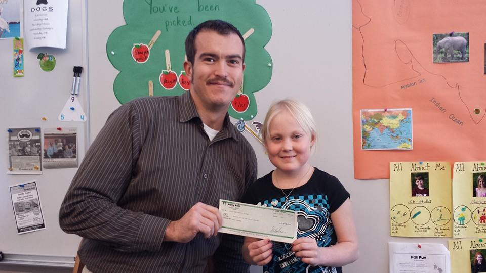 Alpine Bank employee Tom Krabacher presents a check to Soda Creek Elementary School second-grader Jorin Peed. Along with fellow employees Jeremy Behling, David High and Adam Alspach, Krabacher grew a mustache to help Peed out with her medical expenses. People voted for their favorite or least favorite mustache by placing money in a jar. The check totaled $3,099.38. Jorin has been diagnosed with nephritic syndrome, an autoimmune disorder that causes her immune system to attack her kidneys. There is a benefit account in Jorin's name at Alpine Bank.