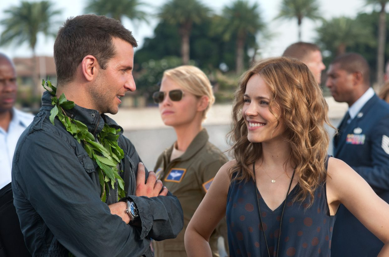 """Brian Gilcrest and ex-girlfriend Tracy Woodside (Bradley Cooper, Rachel McAdams) catch u pon old times while Capt. Allison Ng (Emma Stone) stands at attention in """"Aloha."""" The movie is about a military contractor who is forced to confront old mistakes and possibly find new love while on assignment in Hawaii."""