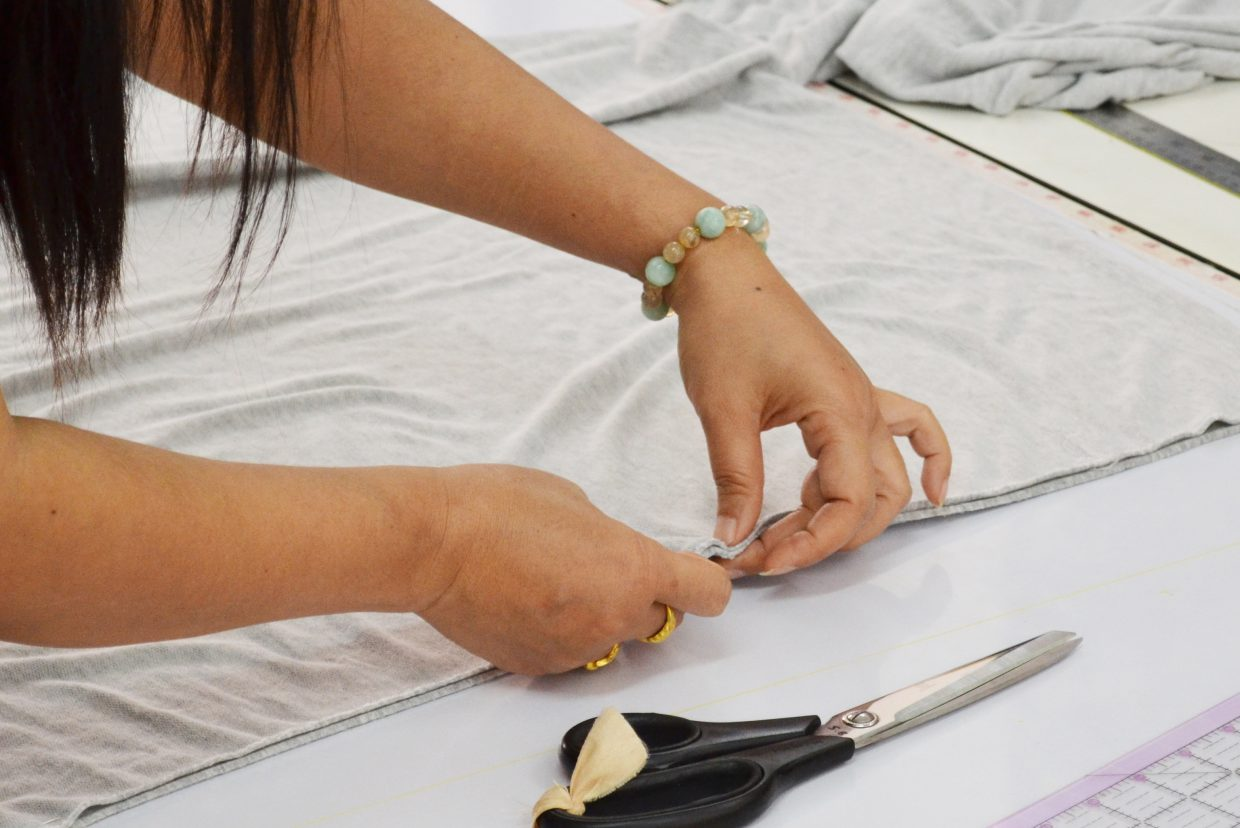 A woman from NightLight Designs works on an Awaken Fair Trade product.