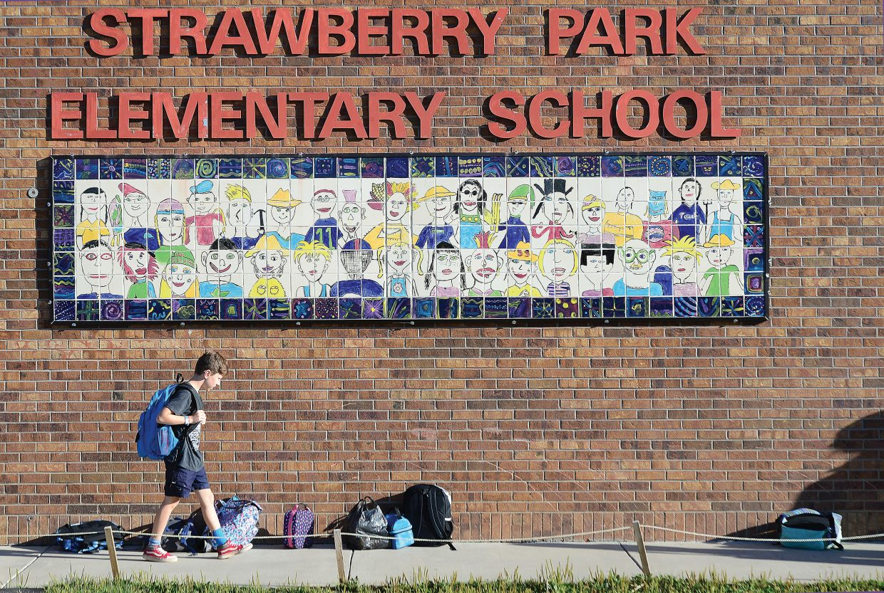 Guinness Elwood walks past the sign on the side of the Strawberry Park Elementary School building on his way back to class Tuesday morning. Elwood will be a fourth grader at Strawberry Park this year.