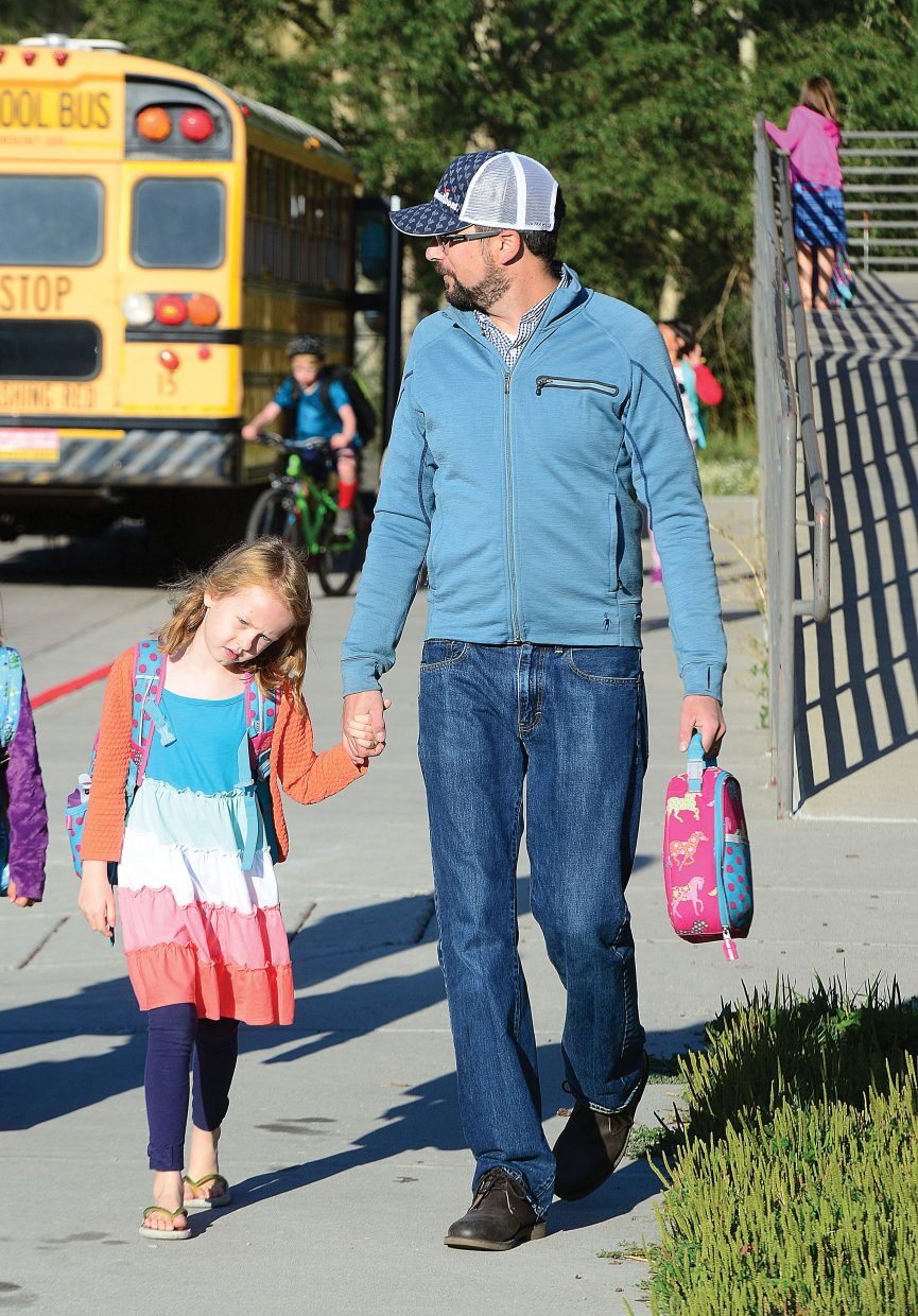 Lee Lapine escorts his daughter Jane back to school at Strawberry Park Elementary School Tuesday for the first day of classes. Jane is entering the first grade.