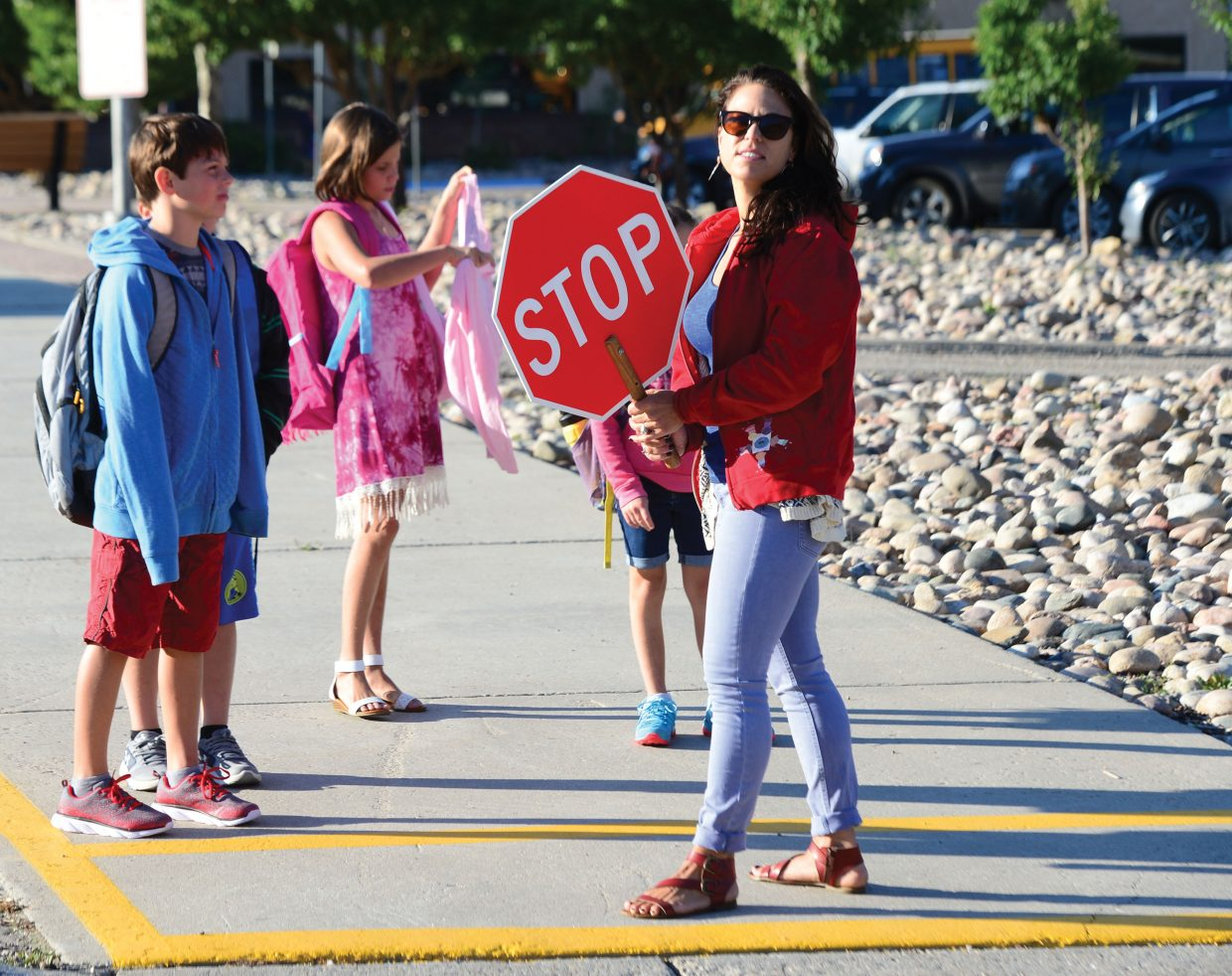 Art teacher Erin Kreis played the role of crossing guard Tuesday morning as students returned to Strawberry Park Elementary School in Steamboat Springs. The day officially marked the end of the summer break as students returned for the start of a 2017-18 school year.