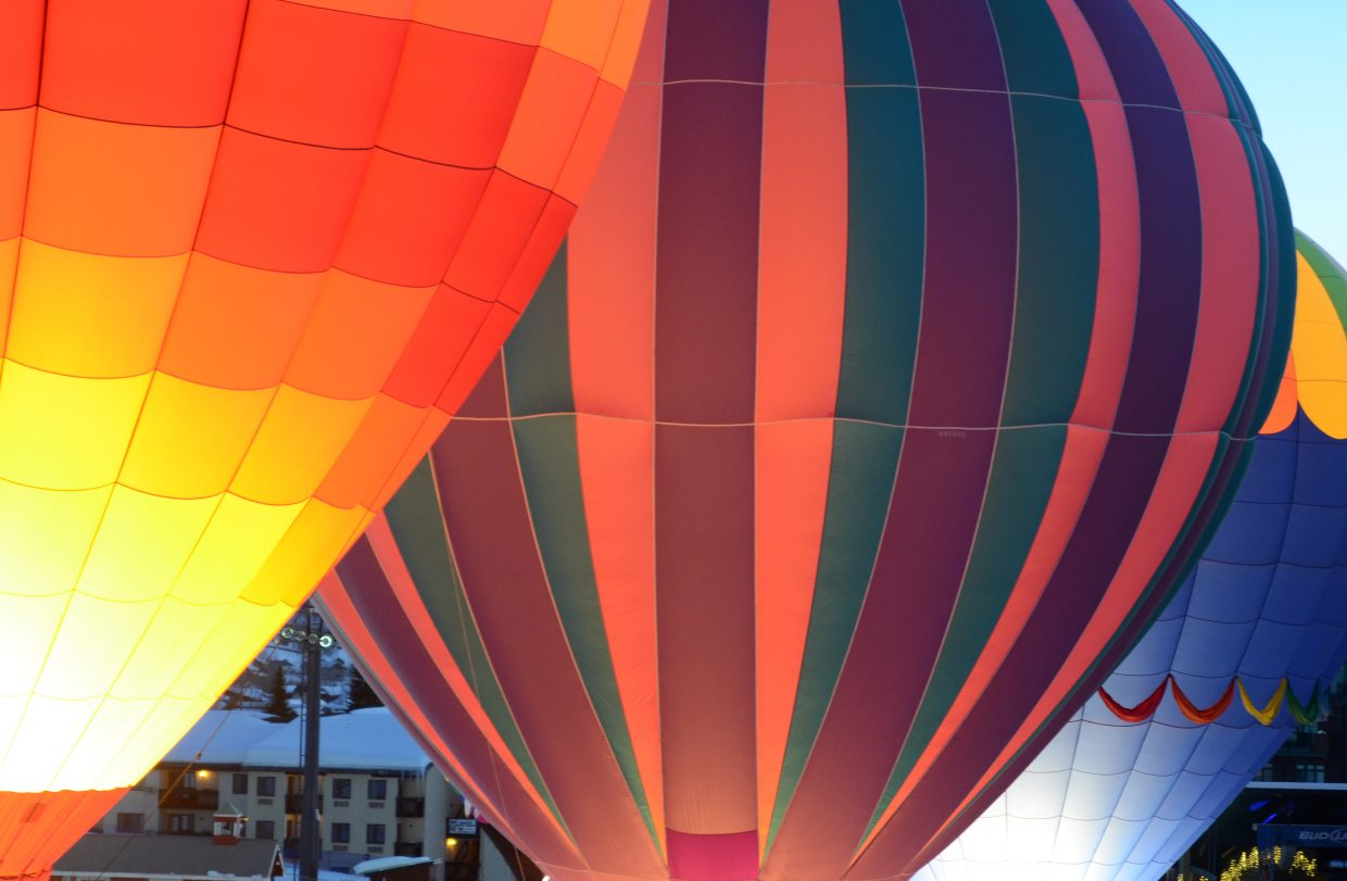 A trio of hot air balloons light up at the base of Steamboat Ski Area on Sunday evening, marking the start of the 41st annual Cowboy Downhill.