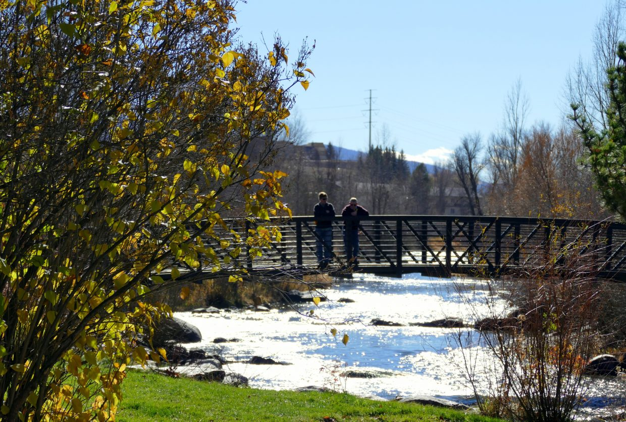 """Two men standing on a bridge over the Yampa River in Steamboat Springs."" Shannon Lukens."