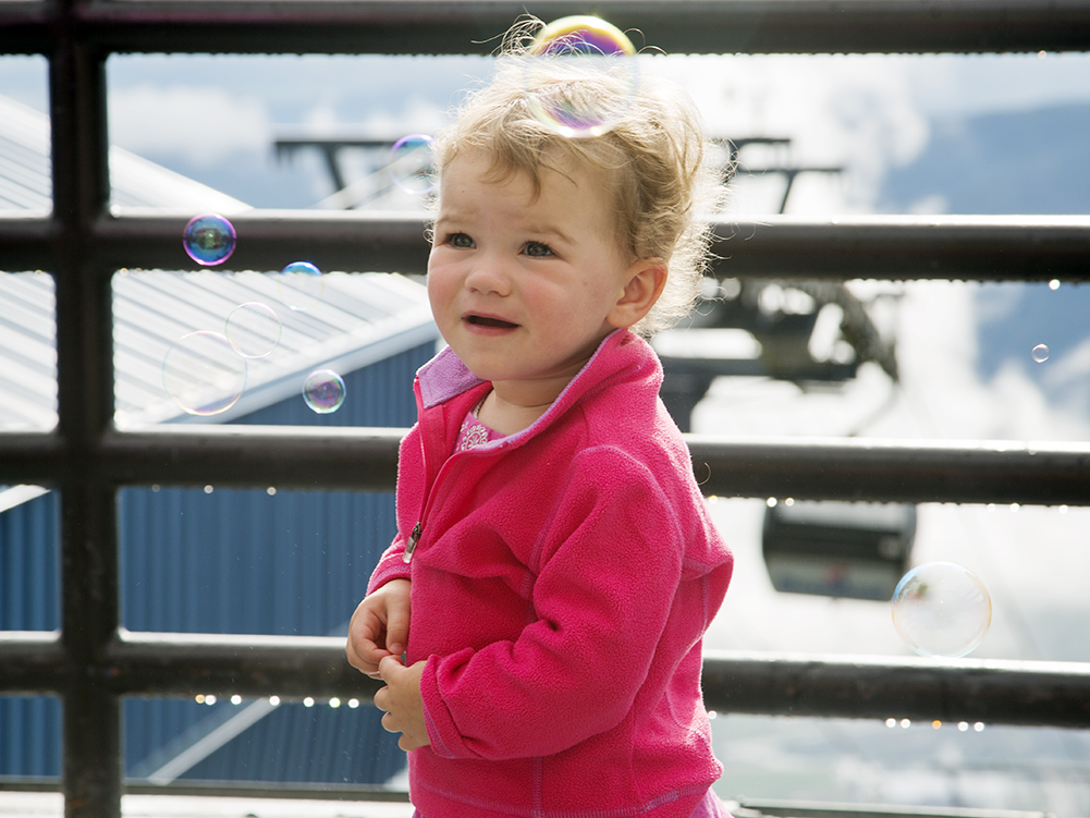 Littleton's Poppy Cuthbert, 17 months old, is fascinated by the bubbles being blown by Wheat Ridge's Eric Shannon on Sunday during the Happy Hour Sunset on the Thunderhead patio in Steamboat Springs.
