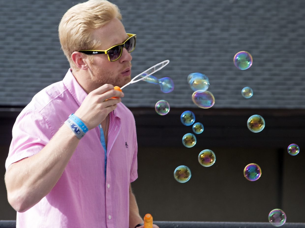 Eric Shannon, of Wheat Ridge, blows bubbles Sunday on the Thunderhead patio during Sunset Happy Hour on the mountain.