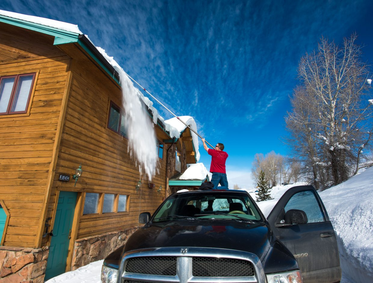 Electing to stay safe, Carl Walker stays off the roof while utilizing his truck and a snow removal tool to ease the burden of the heavy snow on his rental home in Steamboat. Submitted by Carl Walker.