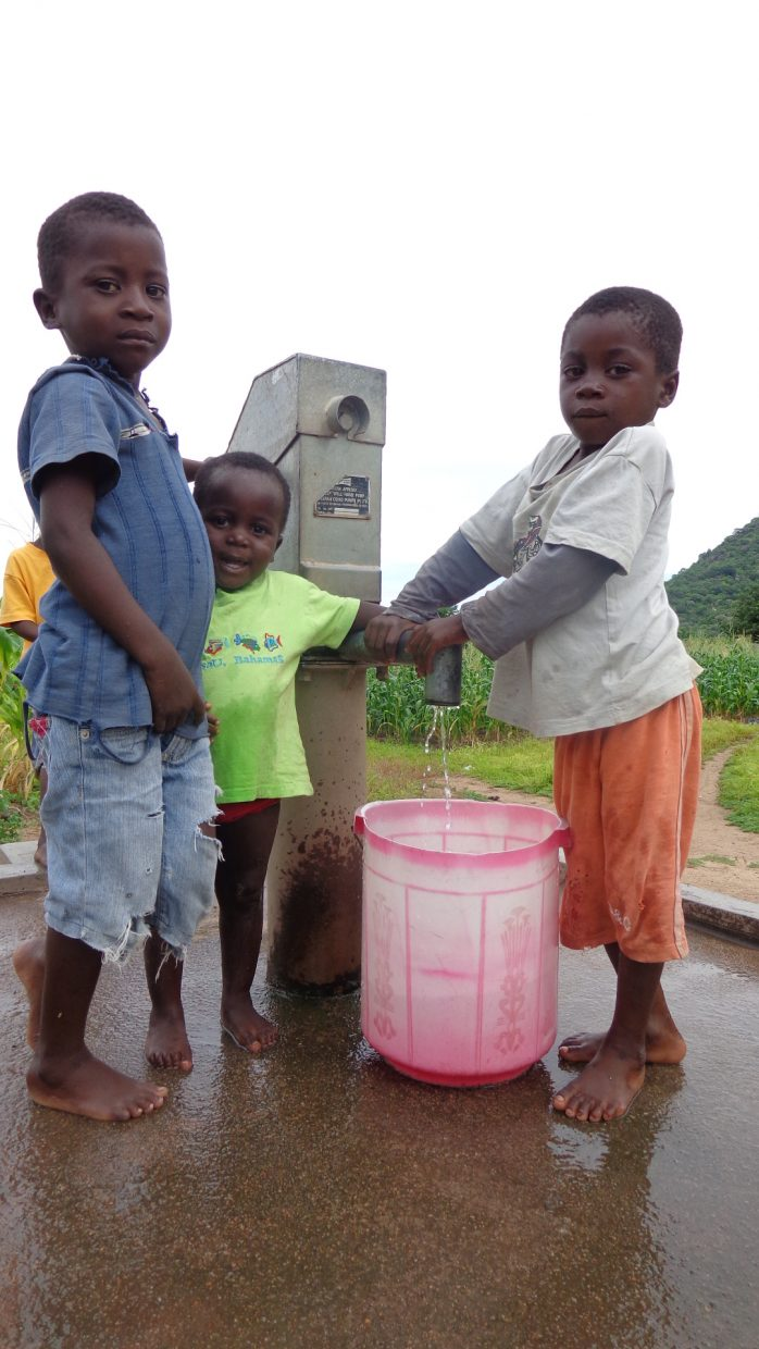 Three little boys in Malawi gather water from a clean water project developed by community members of Steamboat Springs
